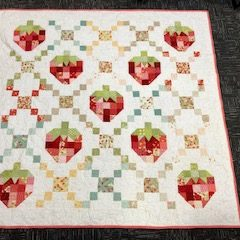 A quilt with a diamond and strawberry design